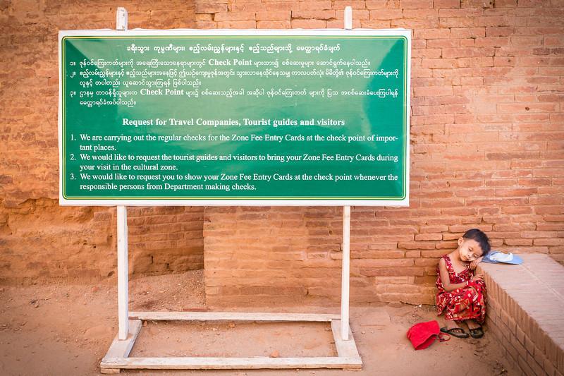Little girl sleeping next to signboard