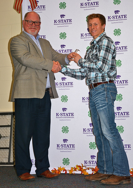 Jerry Dreher of Emprise Bank presents Cooper Jaro with an award for excellent service as a 4-H treasurer.