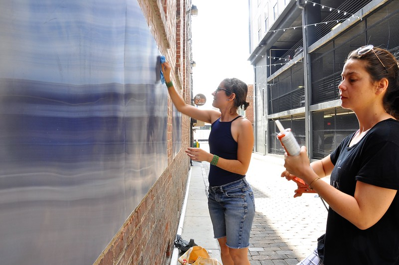 "Eszter Sziksz ( balck shirt) Stephanie Cosby ( blue shirt) work on ""Skywalker"" in Barboro Alley"
