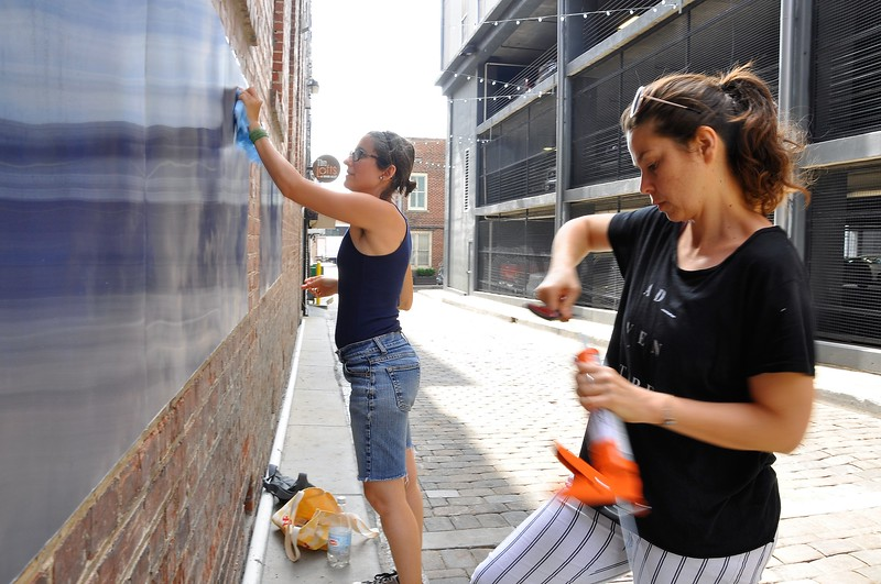 "Eszter Sziksz ( balck shirt) Stephanie Cosby ( blue shirt) work on ""Skywalker"" in Barboro Alley"