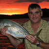 Paul posses with a gold spot trevally with a burning sky behind