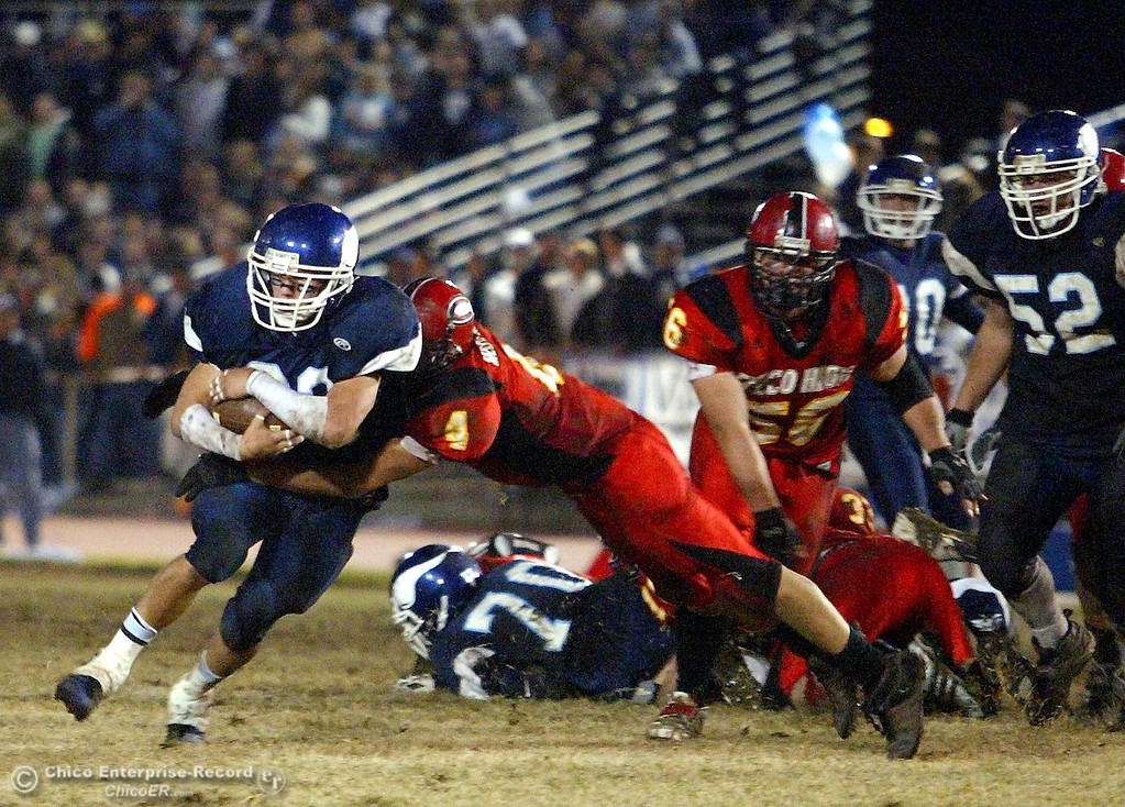 . Pleasant Valley High\'s #32 Evan Busby (left) is tackled by Chico High\'s #4 Andrew Medearis (center) with about 5:42 remaining in the second quarter of their Almond Bowl XXXVII football game at CSUC University Stadium on Friday, October 12, 2007 in Chico, CA.  (Jason Halley/Chico Enterprise-Record)
