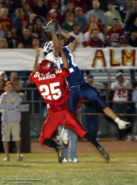 . PV\'s #24 Taylor Clements reaches up to complete a pass near the 20yrd line for a first down as Chico\'s #25 Seth Mares tries to take the ball away during the Almond Bowl Friday night. - halley photo 10/14/05
