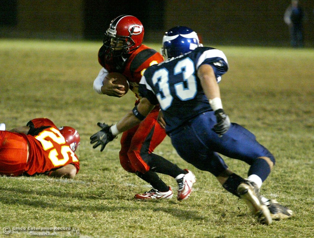. Chico High\'s #20 Brett Scott (center) is tackled by PV High\'s #33 Nick Decaneva (right) near the 30yrd line with about 0:28 remaining in the first quarter in the 2006 Almond Bowl XXXVI football game at University Stadium Friday night. - halley photo 10/13/06