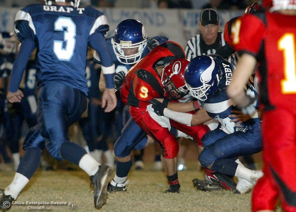 . Chico High\'s #9 Luis Santos (center) is tackled by PV High\'s #55 Logan Hord (center left) and #32 Evan Busby (right) with about 1:21 remaining in the first quarter in the 2006 Almond Bowl XXXVI football game at University Stadium Friday night. - halley photo 10/13/06