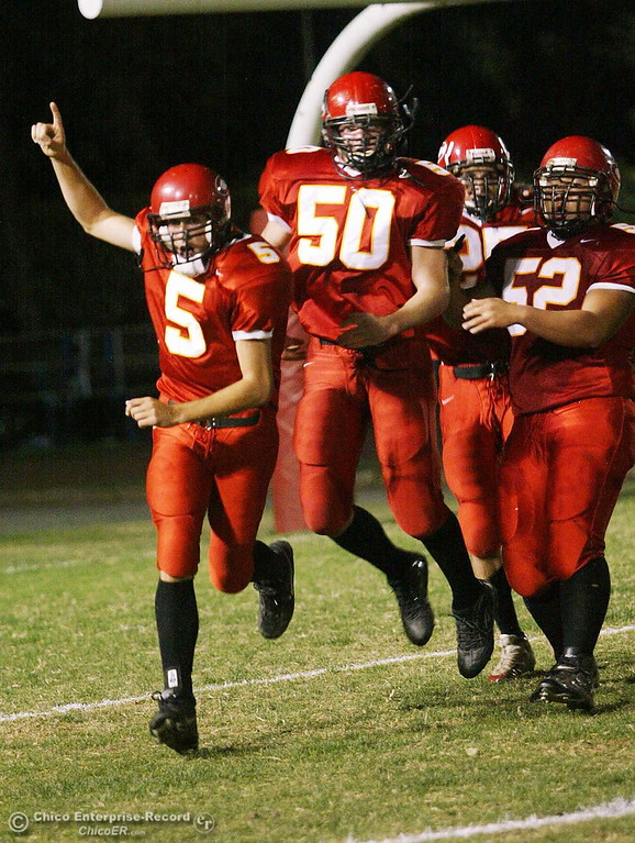 . Chico High QB Will Camy celebrates his rushing touchdown with DE Rory Vernau(50), DB Seth Mares(25) and DL Zzong Mua(52) in the first half against Pleasant Valley in the 2004 Almond Bowl Friday night at University Stadium. photo by Glenn Fuentes sports 10/15/04