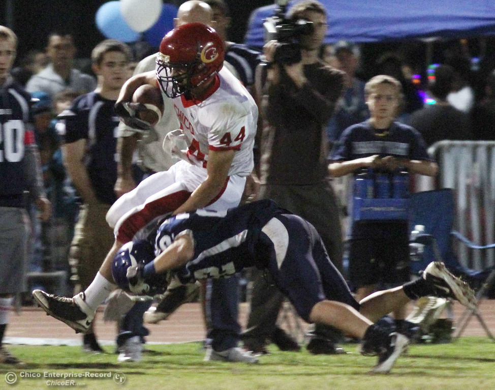. Chico High\'s #44 Mark Jorgensen (left) is tackled against Pleasant Valley High\'s #22 Michael Gerlach (right) in the first quarter during their Almond Bowl XLI football game at CSUC University Stadium Friday, October 21, 2011 in Chico, Calif. (Jason Halley/Chico Enterprise-Record)