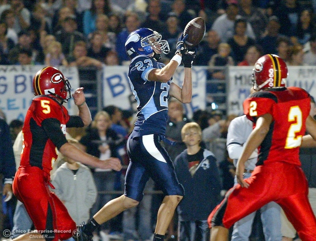 . Chico High\'s #5 Cole Yakemchuk (left) and #2 Terence Ellis (right) watch against Pleasant Valley High\'s #23 Mycal Swaim (center) who completes a catch for a touchdown in the first quarter of their 2008 Almond Bowl Football game Friday, October 17, 2008 at CSUC University Stadium in Chico, CA. 