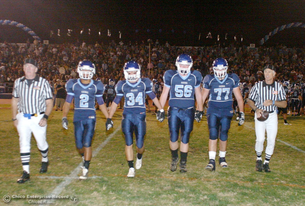 . Chico High against Pleasant Valley High\'s #2 Logan Valencia, #34 Joey Ruth, #56 Kenny Young, and #77 Jordan Rigsbee (left to right) walk onto the field for the coin toss in the first quarter of their Almond Bowl football game at CSUC University Stadium Friday, October 16, 2009 in Chico, Calif. (Jason Halley/Chico Enterprise-Record)