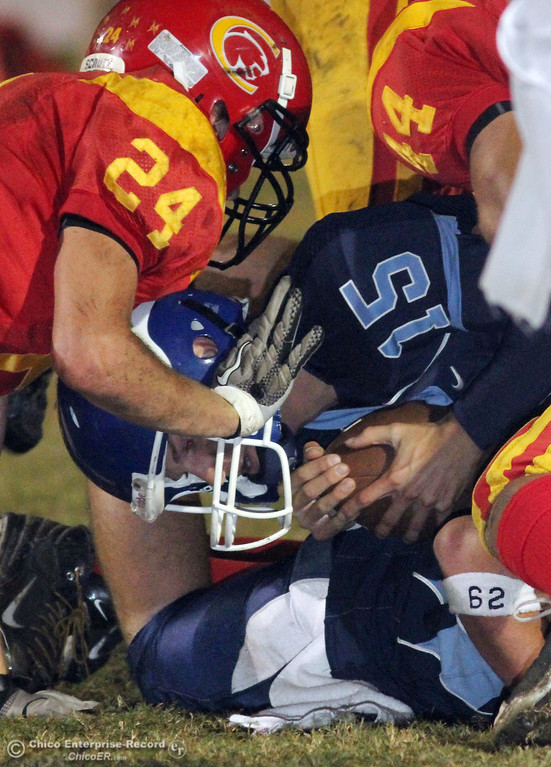 . Pleasant Valley High\'s #15 Will Christensen (center) runs the ball against Chico High\'s #24 Kyle Twisselman (top) in the first quarter of their Almond Bowl football game at CSUC University Stadium Friday, October 22, 2010 in Chico, Calif.