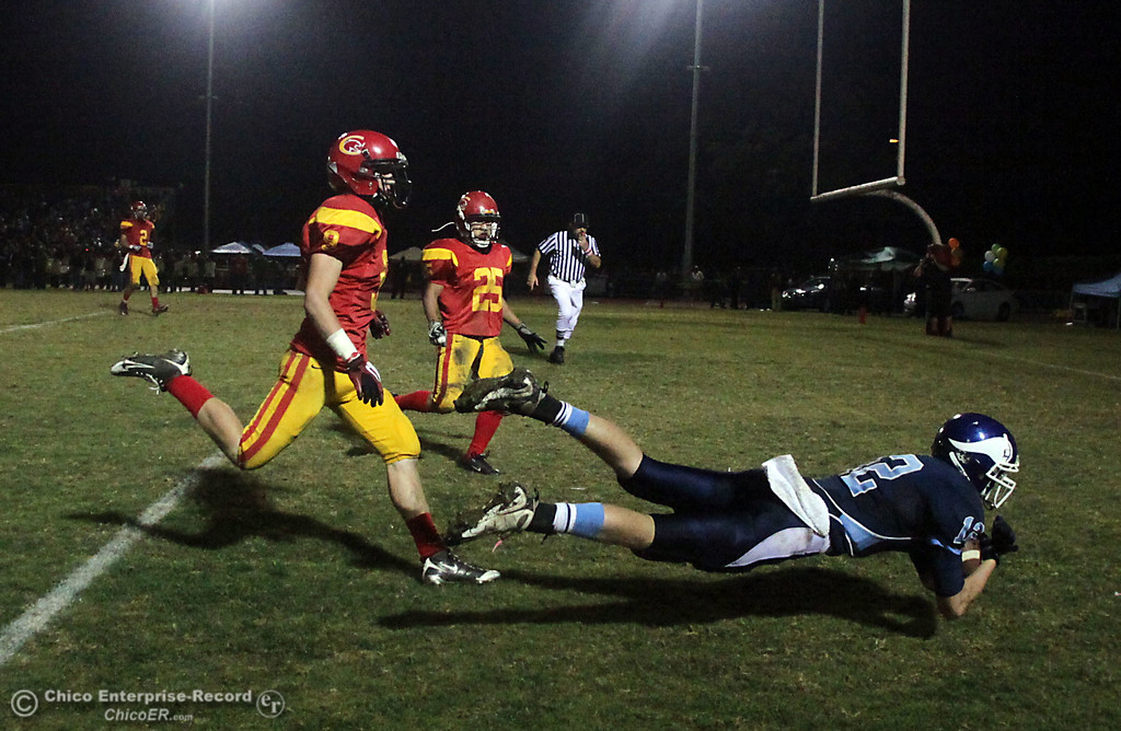 . Pleasant Valley High\'s #12 Chase Drews (right) lays out for a completed catch in the endzone to score a touchdown against Chico High\'s #25 Ger Lee (center) and #9 Jesse Holmes (left) in the second quarter of their Almond Bowl football game at CSUC University Stadium Friday, October 22, 2010 in Chico, Calif.