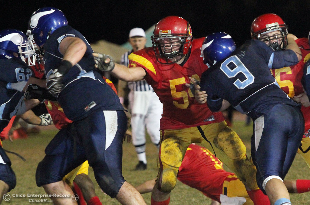 . Pleasant Valley High against Chico High\'s #54 Mike Davis (center) defends in the second quarter of their Almond Bowl football game at CSUC University Stadium Friday, October 22, 2010 in Chico, Calif.