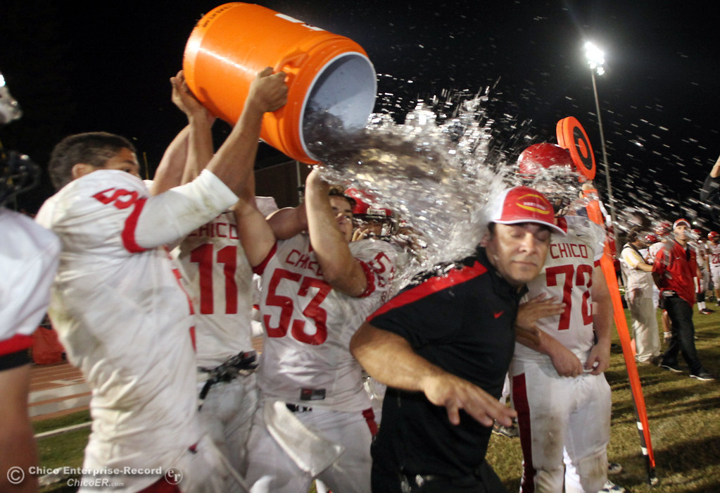 . Chico High\'s #5 Trevon Reid (left) and others pour a bucket of Gatorade on head coach Jason Alvistur (right) on a victory against Pleasant Valley High in the fourth quarter during their Almond Bowl XLI football game at CSUC University Stadium Friday, October 21, 2011 in Chico, Calif. (Jason Halley/Chico Enterprise-Record)