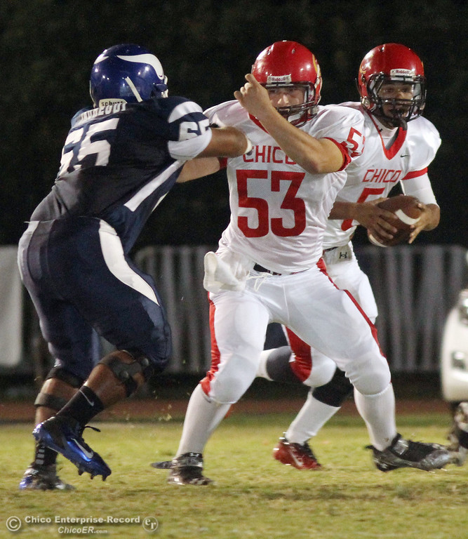 . Chico High\'s #5 Trevon Reid (right) scrambles on a block by #53 Adam Rose (center) against Pleasant Valley High\'s #65 Carlos Jauregui (left) in the first quarter during their Almond Bowl XLI football game at CSUC University Stadium Friday, October 21, 2011 in Chico, Calif. (Jason Halley/Chico Enterprise-Record)