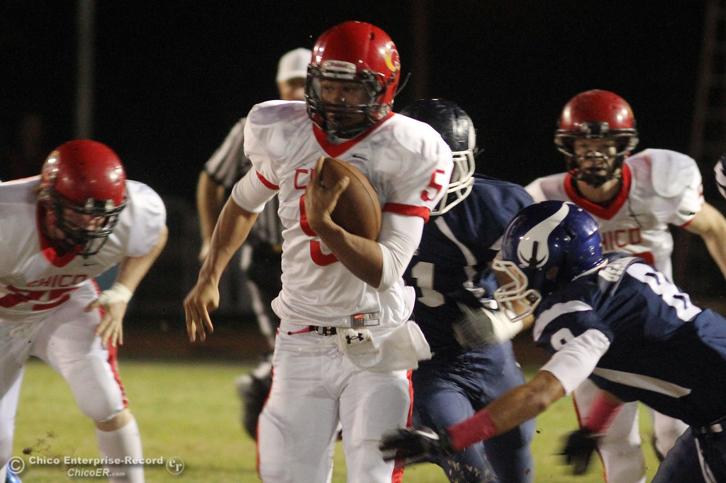 . Chico High\'s #5 Trevon Reid (center) rushes against Pleasant Valley High\'s #8 Tommy Dearmond (right) in the first quarter during their Almond Bowl XLI football game at CSUC University Stadium Friday, October 21, 2011 in Chico, Calif.
