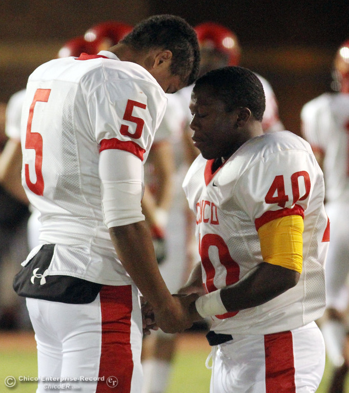 . Chico High\'s #5 Trevon Reid (left) and #40 Ricky Greenwade say a prayer as they ready against Pleasant Valley High before the first quarter during their Almond Bowl XLI football game at CSUC University Stadium Friday, October 21, 2011 in Chico, Calif. (Jason Halley/Chico Enterprise-Record)