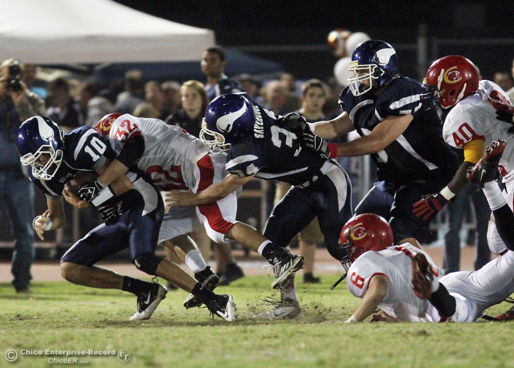 . Chico High\'s #32 Kevin Young (center) tackles against Pleasant Valley High\'s #10 Eric Ascencio (left) in the second quarter during their Almond Bowl XLI football game at CSUC University Stadium Friday, October 21, 2011 in Chico, Calif. (Jason Halley/Chico Enterprise-Record)