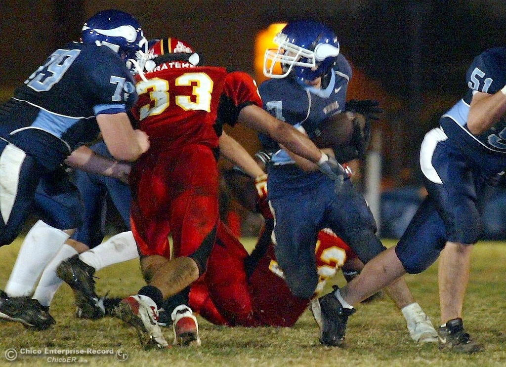 . Chico High\'s #33 Kayhan Karatekeli (left) goes in to tackle against Pleasant Valley High\'s #7 Brandon Nickas (right) whose helmet was spun around in the first quarter of their 2008 Almond Bowl Football game Friday, October 17, 2008 at CSUC University Stadium in Chico, CA. 