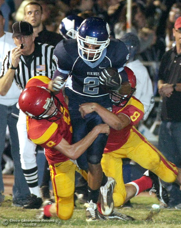 . Chico High\'s #9 Corrie Emmons (left) and #8 Bryson Fricke (right) tackles against Pleasant Valley High\'s #2 Joe Valencia (center) in the first quarter of their Almond Bowl football game at CSUC University Stadium Friday, October 16, 2009 in Chico, Calif. (Jason Halley/Chico Enterprise-Record)
