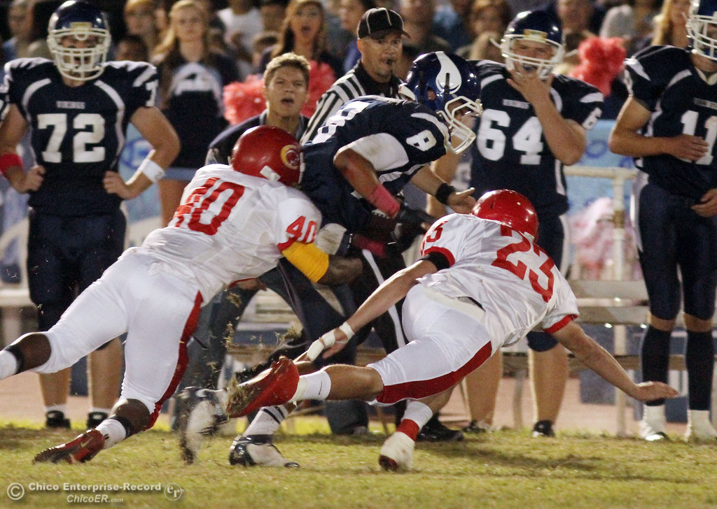 . Chico High\'s #40 Ricky Greenwade (left) and #23 Seth Webster (right) tackle against Pleasant Valley High\'s #8 Tommy Dearmond (center) in the first quarter during their Almond Bowl XLI football game at CSUC University Stadium Friday, October 21, 2011 in Chico, Calif. (Jason Halley/Chico Enterprise-Record)