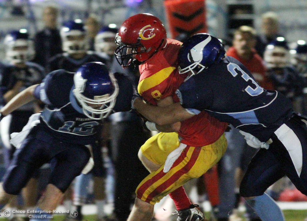. Pleasant Valley High\'s #12 Chase Drews (left) and #3 Gary Hemmingsen (right) tackle against Chico High\'s #9 Jesse Holmes (center) in the first quarter of their Almond Bowl football game at CSUC University Stadium Friday, October 22, 2010 in Chico, Calif.