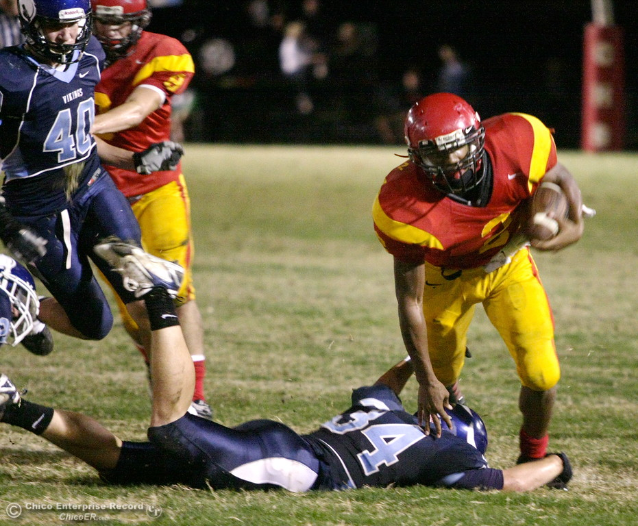 . Chico High\'s #2 Jamiel Hardman (right) is tackled against Pleasant Valley High\'s #34 Joey Ruth (bottom) in the first quarter of their Almond Bowl football game at CSUC University Stadium Friday, October 16, 2009 in Chico, Calif. (Jason Halley/Chico Enterprise-Record)