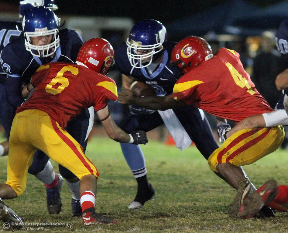 . Pleasant Valley High\'s #3 Gary Hemmingsen (center) rushes against Chico High\'s #6 Tanner Trimm (left) and #4 Jamiel Hardman (right) in the first quarter of their Almond Bowl football game at CSUC University Stadium Friday, October 22, 2010 in Chico, Calif.