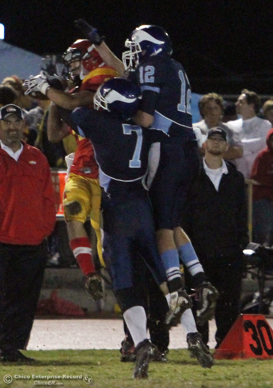 . Pleasant Valley High\'s #7 Kyle Forbis (center) and #12 Chase Drews (right) attempt to defend against Chico High\'s #2 Aaron Chu (left) who completes a catch in the first quarter of their Almond Bowl football game at CSUC University Stadium Friday, October 22, 2010 in Chico, Calif.