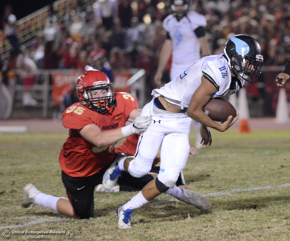 . Chico\'s Cody Billson (35) hangs on to tackle Pleasant Valley\'s Quaine Rhodes (12) during the Almond Bowl on Friday, Oct. 21, 2016, at University Stadium in Chico, California.