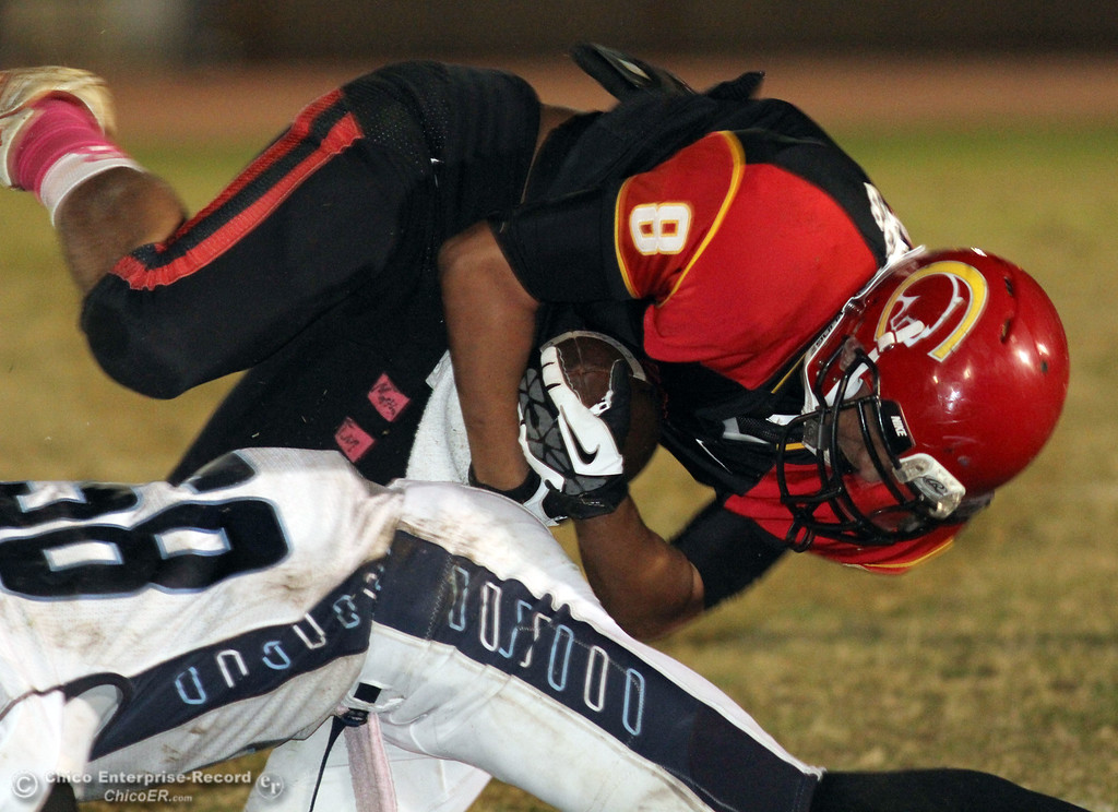 . Chico High\'s #8 Jesse Chambers (top) is tackled against Pleasant Valley High\'s #85 Trey Rosenbalm (bottom) in the fourth quarter of their Almond Bowl football game at CSUC University Stadium Friday, October 26, 2012 in Chico, Calif. (Jason Halley /Chico Enterprise-Record)