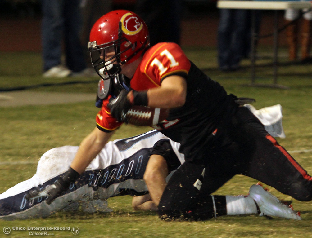 . Chico High\'s #11 Jesse Holmes (right) is tackled in the endzone for a touchdown off a interception against Pleasant Valley High\'s #40 Sam Savercool (bottom) in the second quarter of their Almond Bowl football game at CSUC University Stadium Friday, October 26, 2012 in Chico, Calif. (Jason Halley /Chico Enterprise-Record)