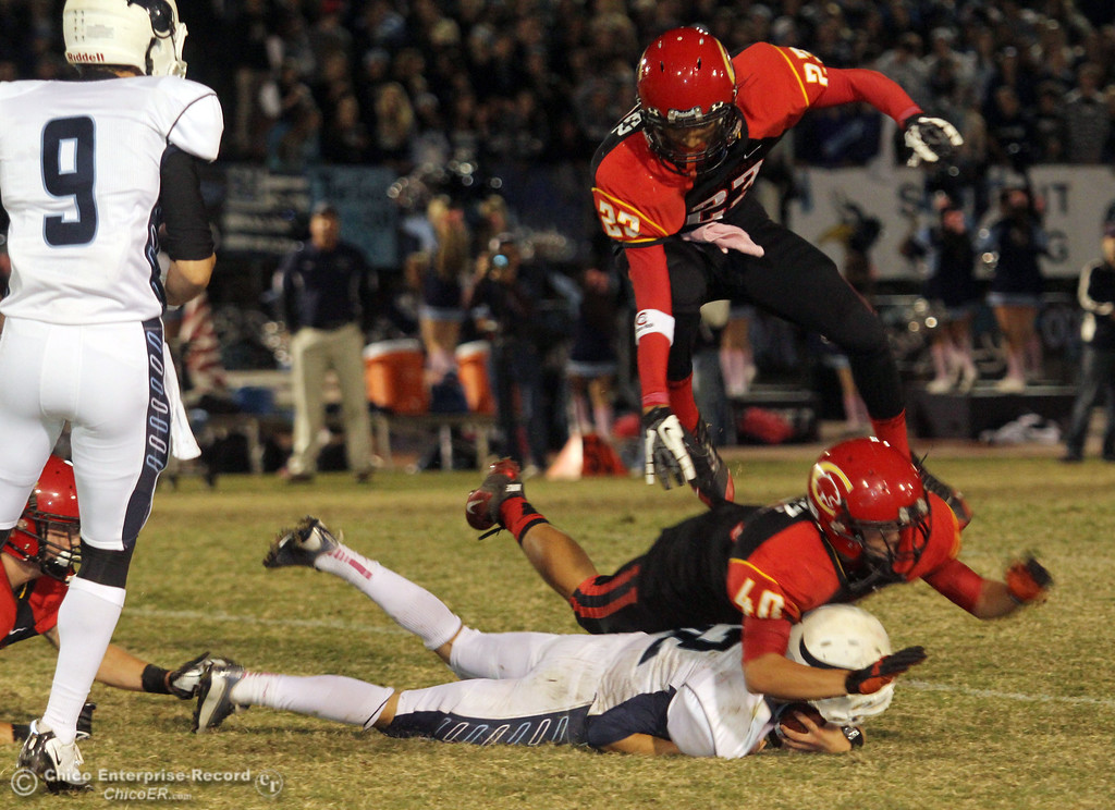 . Chico High\'s #23 Donovan Sanchez (top) and #40 Andrew Morgan-Hernandez (center) tackles against Pleasant Valley Highs\' #12 Gregory Darms (bottom) in the second quarter of their Almond Bowl football game at CSUC University Stadium Friday, October 26, 2012 in Chico, Calif. (Jason Halley /Chico Enterprise-Record)