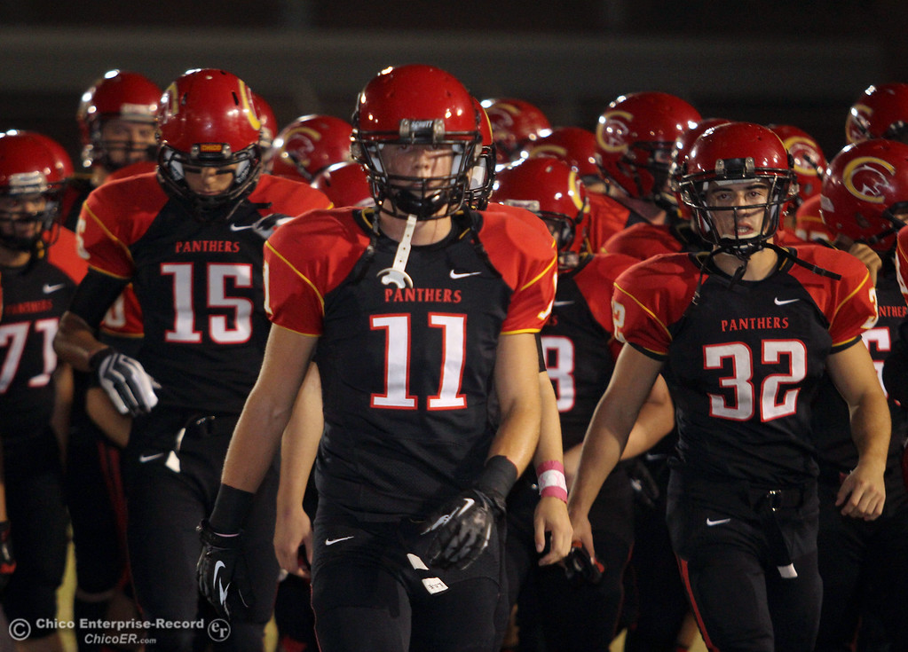. Chico High\'s #11 Jesse Holmes and others take the field against Pleasant Valley High in the first quarter of their Almond Bowl football game at CSUC University Stadium Friday, October 26, 2012 in Chico, Calif. (Jason Halley /Chico Enterprise-Record)