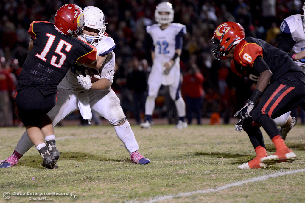 . Chico\'s Miles Fishback (15) holds up Pleasant Valley\'s Anthony Jensen (15) until Kehmarr Mcmillian (8) and other Panthers can help with the tackle on third down in overtime Friday, Oct. 24, 2014, during the Almond Bowl in Chico, California.
