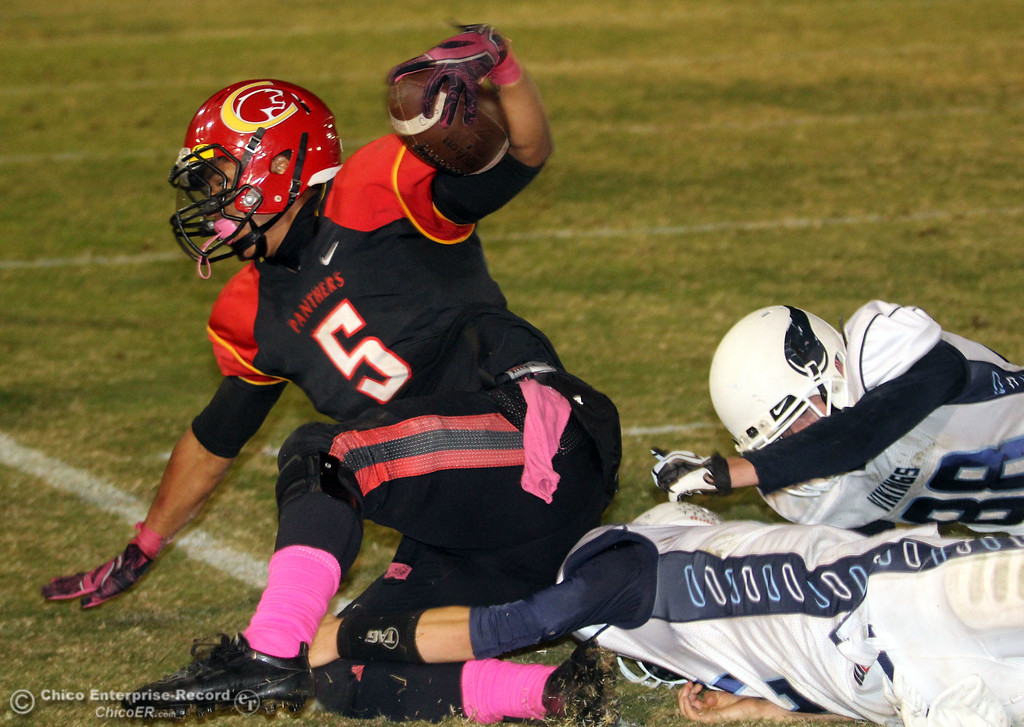 . Chico High\'s #5 Trevon Reid (left) is tackled against Pleasant Valley High\'s #12 Gregory Darms (bottom) and #88 Ryan Troudy (right) in the second quarter of their Almond Bowl football game at CSUC University Stadium Friday, October 26, 2012 in Chico, Calif. (Jason Halley /Chico Enterprise-Record)