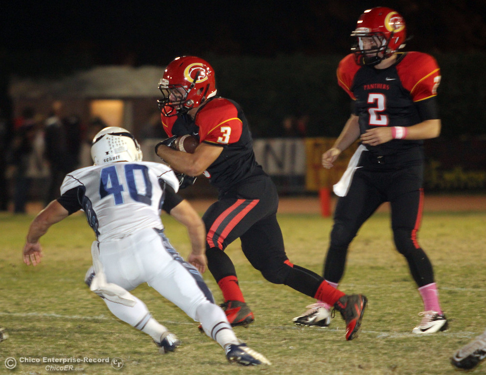 . Chico High\'s #2 Daniel Robbins (right) hands off to #3 Cordero Rios (center) rushes against Pleasant Valley High\'s #40 Sam Savercool (left) in the first quarter of their Almond Bowl football game at CSUC University Stadium Friday, October 26, 2012 in Chico, Calif. (Jason Halley /Chico Enterprise-Record)