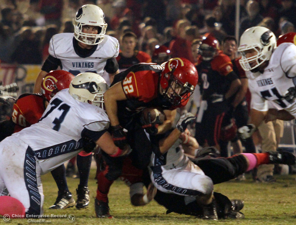 . Chico High\'s #32 KJ Young (center) rushes against Pleasant Valley High\'s #73 Brandon Maddox (left) in the second quarter of their Almond Bowl football game at CSUC University Stadium Friday, October 26, 2012 in Chico, Calif. (Jason Halley /Chico Enterprise-Record)