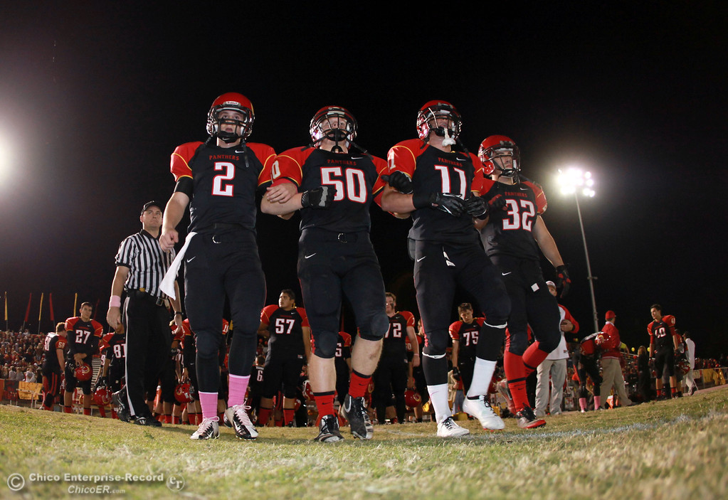 . Chico High\'s #2 Daniel Robbins, #50 Sam Miller, #11 Jesse Holmes, and #32 KJ Young (left to right) take the field for the coin toss against Pleasant Valley High in the first quarter of their Almond Bowl football game at CSUC University Stadium Friday, October 26, 2012 in Chico, Calif. (Jason Halley /Chico Enterprise-Record)