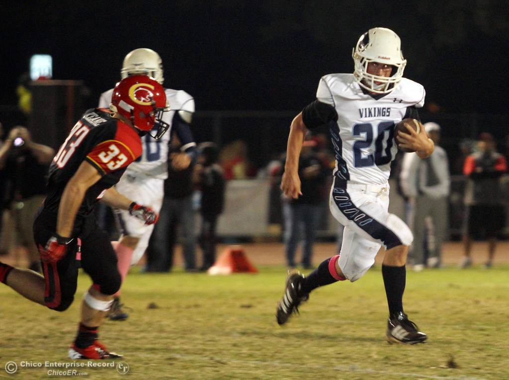 . Chico High\'s #33 Kyle Keane (left) defends against Pleasant Valley High\'s #20 Matt Price (right) rushes in the second quarter of their Almond Bowl football game at CSUC University Stadium Friday, October 26, 2012 in Chico, Calif. (Jason Halley /Chico Enterprise-Record)