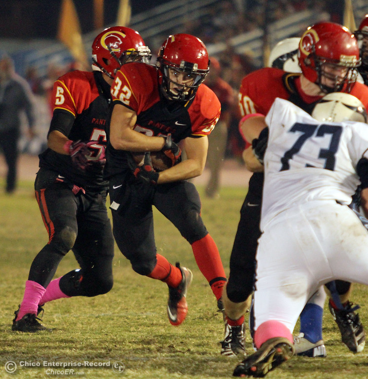 . Chico High\'s #5 Trevon Reid (left) hands off to #32 KJ Young (right) against Pleasant Valley High in the second quarter of their Almond Bowl football game at CSUC University Stadium Friday, October 26, 2012 in Chico, Calif. (Jason Halley /Chico Enterprise-Record)