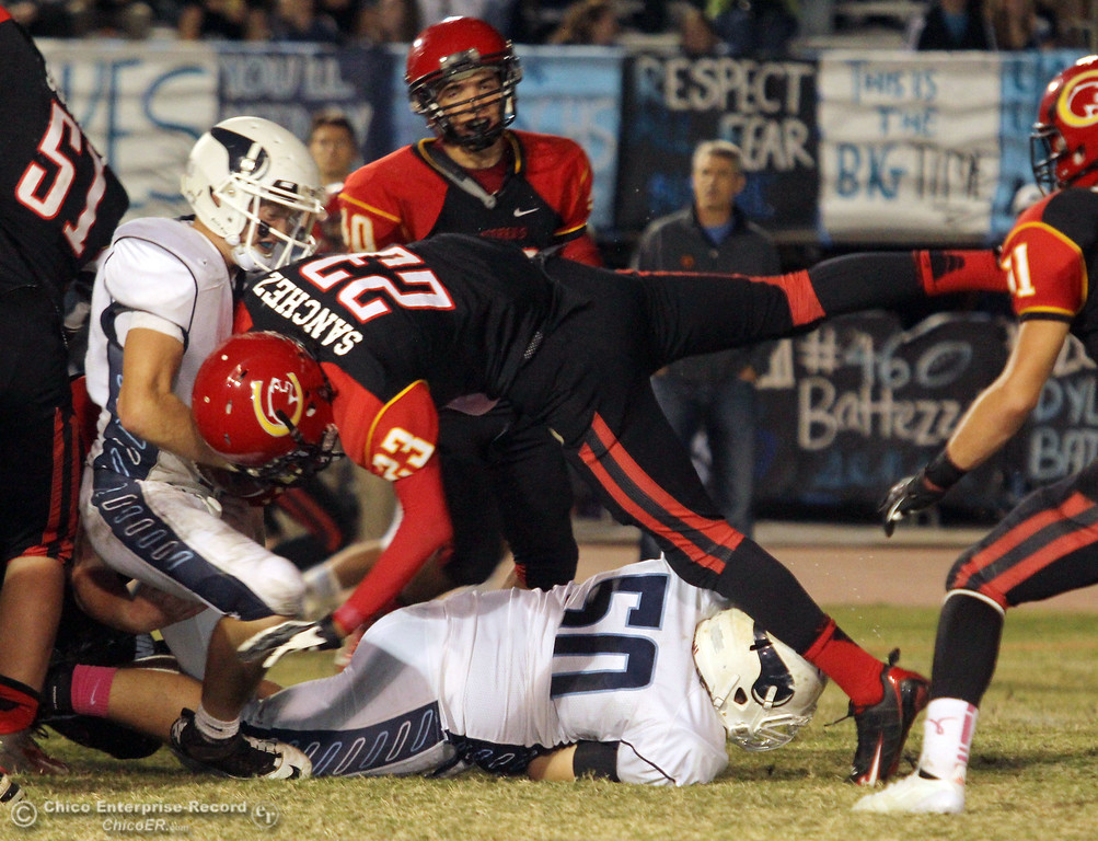 . Chico High\'s #23 Donovan Sanchez (center) puts a stop against Pleasant Valley High in the second quarter of their Almond Bowl football game at CSUC University Stadium Friday, October 26, 2012 in Chico, Calif. (Jason Halley /Chico Enterprise-Record)