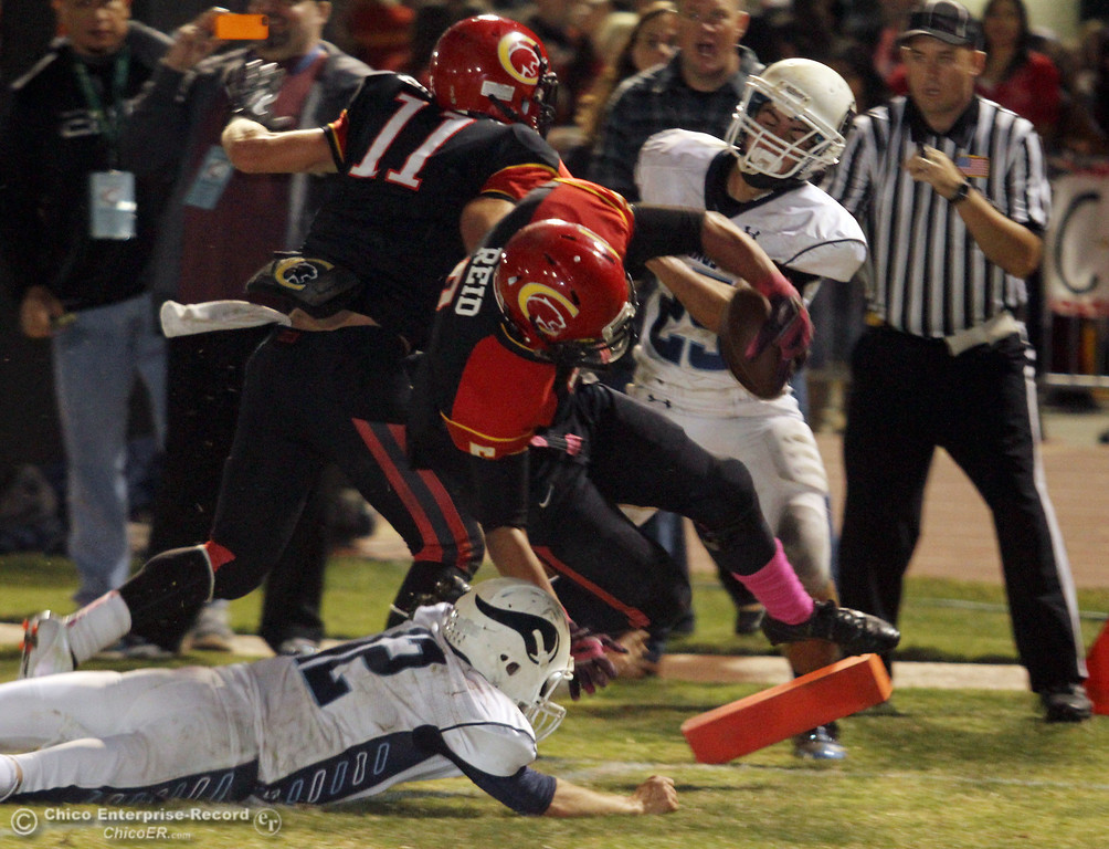 . Chico High\'s #5 Trevon Reid (center) is tackled in the endzone for a touchdown against Pleasant Valley High\'s #12 Gregory Darms (bottom) in the second quarter of their Almond Bowl football game at CSUC University Stadium Friday, October 26, 2012 in Chico, Calif. (Jason Halley /Chico Enterprise-Record)