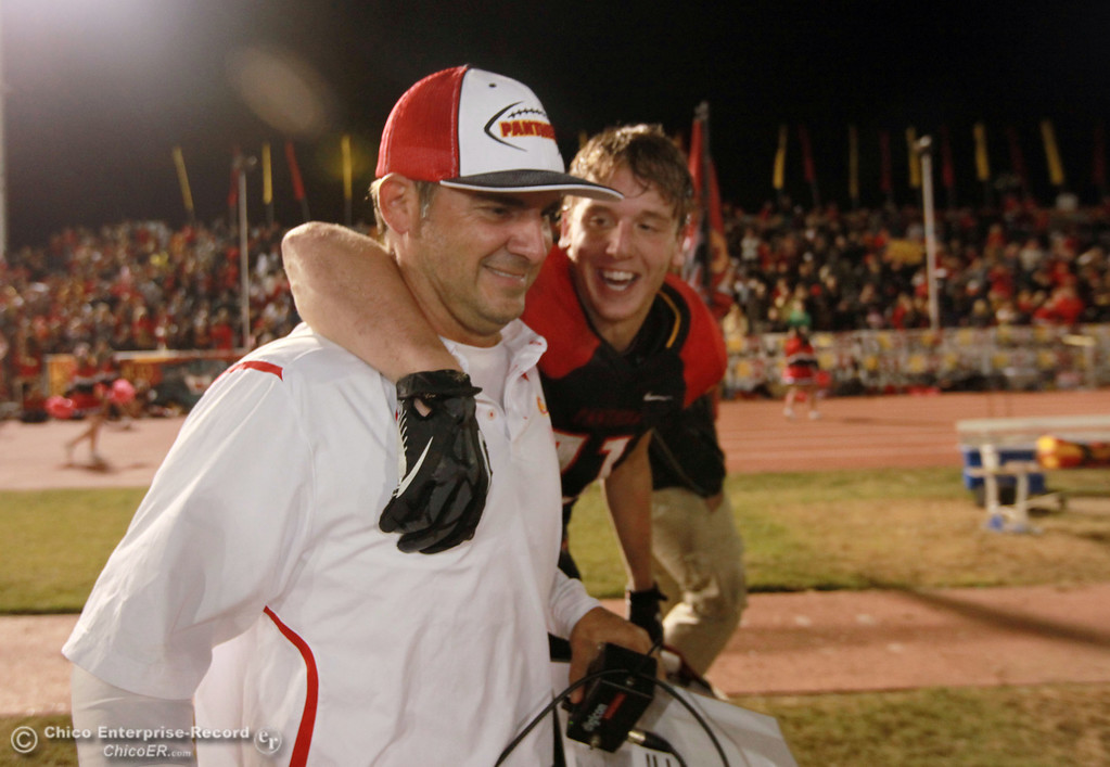 . Chico Highs\' #11 Jesse Holmes (right) celebrates a win with coach Jason Alvistur  against Pleasant Valley High in the fourth quarter of their Almond Bowl football game at CSUC University Stadium Friday, October 26, 2012 in Chico, Calif. (Jason Halley /Chico Enterprise-Record)
