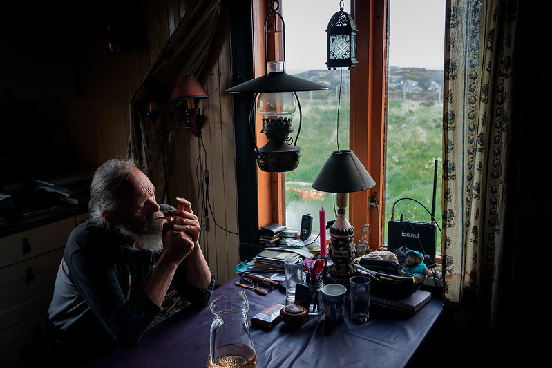 On a small island called Risøy on the Norwegian coast. One couple lives here only. Here the man is in the kitchen. The island has no tapwater or electricity.