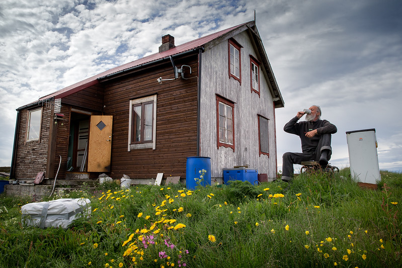 On a small island called Risøy on the Norwegian coast. One couple lives here in the house seen on the photo. The man is outside, drinking coffee.