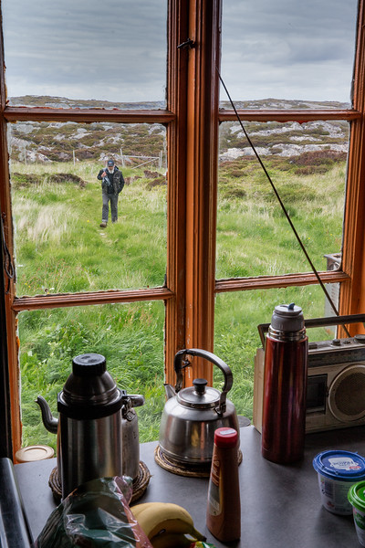 Man seen through window on a small island on the Norwegian coast. The island has no tapwater or electricity.