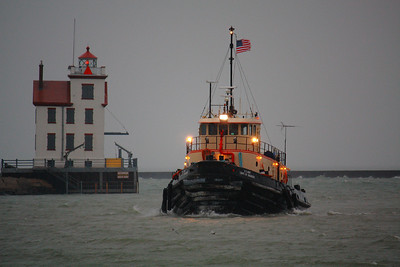 A Tug's Work - Not for Fair Weather Sailors!  Making way through wind and rain, the U.S. Army Corps of Engineers Harbor Tug 'Cheraw' passes the 'West Breakwater Lighthouse' in Lorain, Ohio shortly after sunrise on a windy and rainy morning.