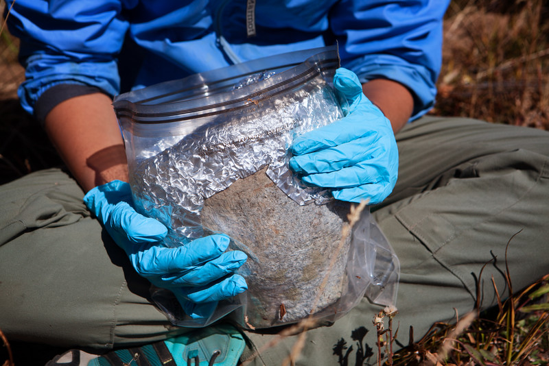 An archaeologist packages a massive soapstone bowl that was found near 11,000 feet. It is covered in tin foil so that the interior is not contaminated before being tested for biomolecular remains of ancient food