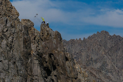 Climbers trying to lasso the Tyrolean traverse on Sun Ribbon Arete, Temple Crag. Sierra Nevada, California.