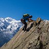 """Climber on the """"Razor's Edge"""" pitch on the Aiguille de la Gliere. Mont Blanc in the background. Chamonix, France."""